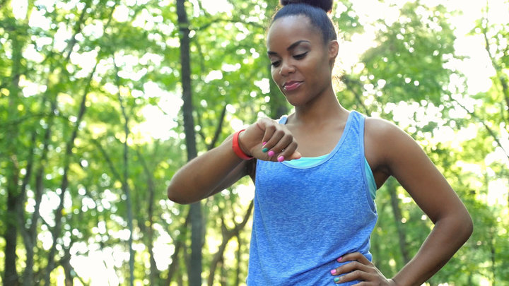 African American athletic woman checking fitbit device after running